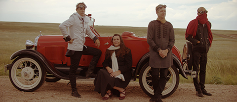 Members of musical ensemble DeVotchKa posing next to an antique open air classic red car on a tan dirt road with goggles and scarves.