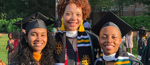 Three graduate smiling for the camera in Commencement robes and the stoles bestowed upon them at the Donning of the Kente ceremony