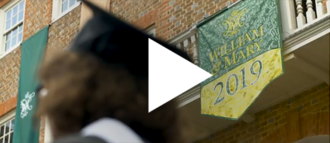 Video still of a graduate standing in front of the William & Mary Class of 2019 banner hanging on the Wren Building