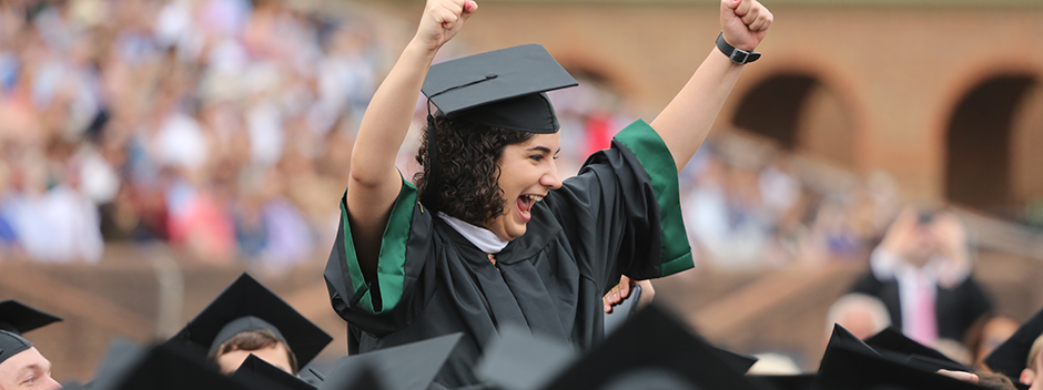 A student pumps two fists in the air in celebration at the main Commencement ceremony