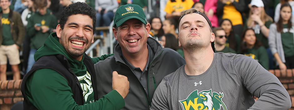 Three men of different ages pose while cheering on the Tribe Football team at Homecoming