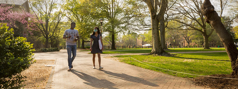 Two masked students walking across campus on a brick walkway