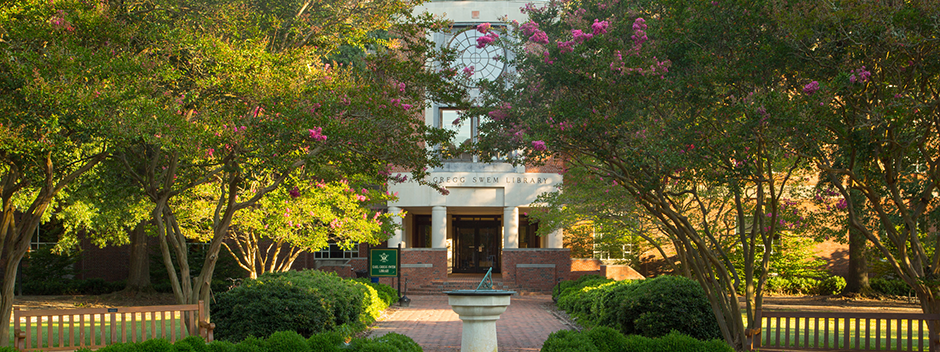 front view of Swem Library including the sundial and early pink blooms on crepe myrtle trees